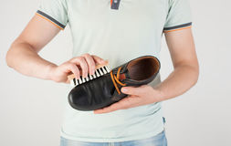 Man holding in hands brush and black boot. Care for leather shoes over white wooden background. The background image place for text Royalty Free Stock Image