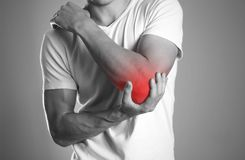 A man holding hands. Pain in the elbow. The hearth is highlighted in red. Close up. Isolated background stock image