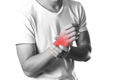 A man holding hands. Pain in the wrist. The hearth is highlighted in red. Close up. Isolated on white background.  stock photography