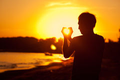 Man holding in hands the setting sun Stock Images