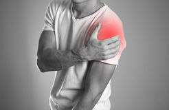 A man holding hands. Shoulder pain. The hearth is highlighted in. Red. Close up. Isolated background stock images