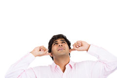 Man holding hands to ears and looking up covering to shut out noise Stock Photography