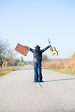Man holding hands up with suitcase and guitar Stock Photography