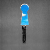 Man holding and hanging on wall with key shape hole Royalty Free Stock Images
