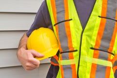 Man Holding Hardhat. Closeup of man holding hardhat with house siding background Stock Photos