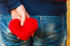 Man holding heart behing his body. Royalty Free Stock Photo