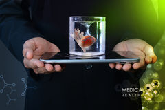 Man is holding a heart in glass of water  and tablet computer Royalty Free Stock Photo