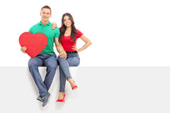 Man holding heart seated on panel with his girlfriend Royalty Free Stock Photography