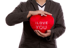 Man holding heart shape pillow. Royalty Free Stock Images
