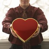 Man holding heart shaped box. Stock Photo