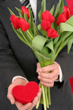 Man Holding Heart Shaped Box and Flowers royalty free stock image