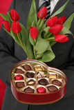 Man Holding Heart Shaped Box and Tulips Royalty Free Stock Photos