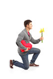 Man holding a heart shaped pillow and flowers Royalty Free Stock Images