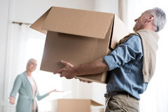 Man holding heavy cardboard box at new home Stock Photos