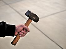 Man holding heavy metal hammer on construction site. royalty free stock photos