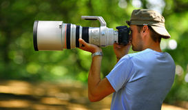Man is holding heavy 400mm f2.8 lens and taking photos Royalty Free Stock Photo