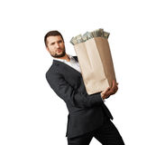 Man holding heavy paper bag with money Stock Photo
