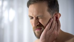 Man holding his aching ear, suffering from otitis, sudden hearing loss, close up stock photography