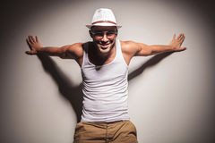 Man holding his arms open on the wall behind him. Royalty Free Stock Photography