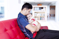 Man holding his baby on the couch Stock Images