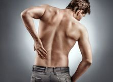 Man holding his back in pain on grey background. stock image