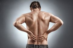 Man holding his back in pain. Medical concept stock image