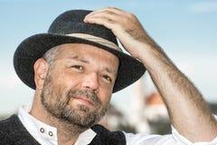 Man holding his Bavarian black hat Royalty Free Stock Image
