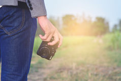 A man holding his camera on meadow. Stock Images