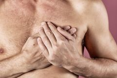 Man holding his chest with both hands, having heart attack or painful cramps, pressing on chest with painful expression on blue ba. Severe heartache, man stock image