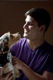 Man Holding His Dog. Low key portrait of a young man holding a cute mixed breed terrier dog isolated over a dark background Stock Photo