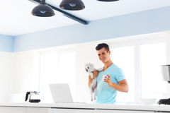 Man holding his dog, standing with a cup of coffee in the kitche Royalty Free Stock Photo