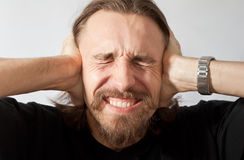 Man holding his ears. Caucasian man holding his ears from noise royalty free stock photography