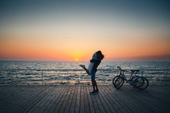 Man holding his girlfriend, couple of young lovers kissing at the beach at sunrise sky at wooden deck summer time royalty free stock images