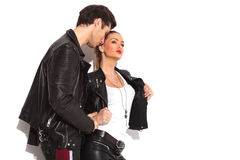 Man holding his girlfriend while she opens her leather jacket. Sexy men holding his girlfriend while she opens her leather jacket and looks away Stock Photography