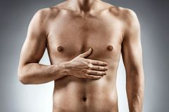 Man holding his hand in area stomach. Digestion issue. Man holding his hand in area stomach. Medical concept Stock Photo
