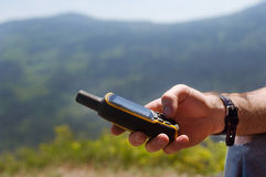 Man holding in his hand GPS. Close up of man holding in his hand GPS navigator, Global Positioning System device. Mountain summer landscape as a background Royalty Free Stock Photos