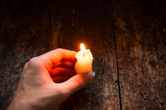 Man holding in his hand a lighted wax candle on a wooden Stock Photos