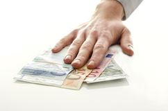 Man holding his hand over Euro banknotes Stock Photography