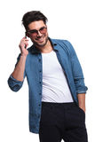 Man holding his hand in pocket while talking on phone. Handsome casual man holding his hand in pocket while talking on the phone, smiling for the camera Royalty Free Stock Photography