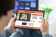 Man holding in his hands computer tablet app delivery food. Man holding in his hands computer tablet with app delivery food on the screen in the house in room stock photography