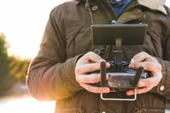 Man holding in his hands remote controller joystick transmitter flying the drone with sun shining bright day outdoors stock photo