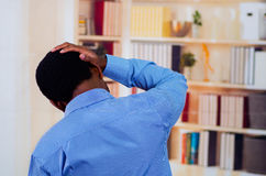 Man holding his head with one hand, feeling pain. View from his back Royalty Free Stock Photo
