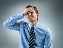Man holding his head in pain. royalty free stock image