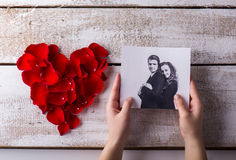 Man holding his and his girlfriends photo. Rose petal heart. Royalty Free Stock Photos
