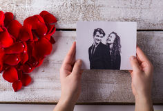 Man holding his and his girlfriends photo. Rose petal heart. Royalty Free Stock Images
