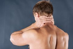 Man holding his neck with both hands, isolated on blue background. Lower neck pain. Shirtless man touching his neck for the pain stock photos