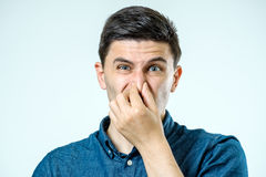 Man holding his nose against a bad smell Stock Images