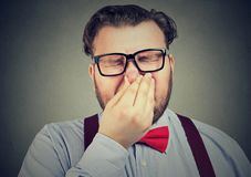 Man holding his nose against a bad smell. Man pinches nose with fingers looks with disgust something stinks isolated on gray wall background. Face expression Stock Photos