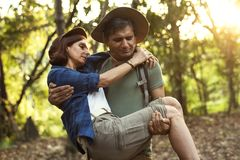 Man holding his partner up while trekking in the jungle Royalty Free Stock Photos