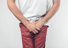A man holding his penis with on the white background. Wants to go to the toilet. Stock Photos